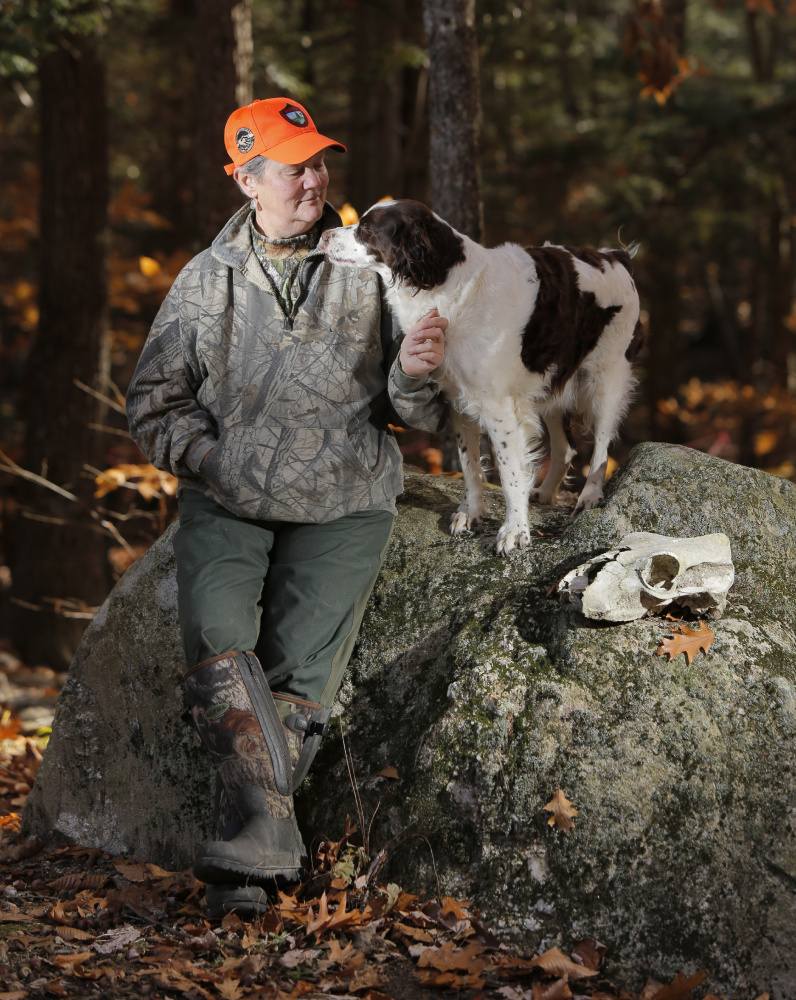 """""""Pink has no place in camouflage,"""" says Georgette Kanach, a longtime hunter and Registered Maine Guide seen in the woods of Gray with her dog Star."""