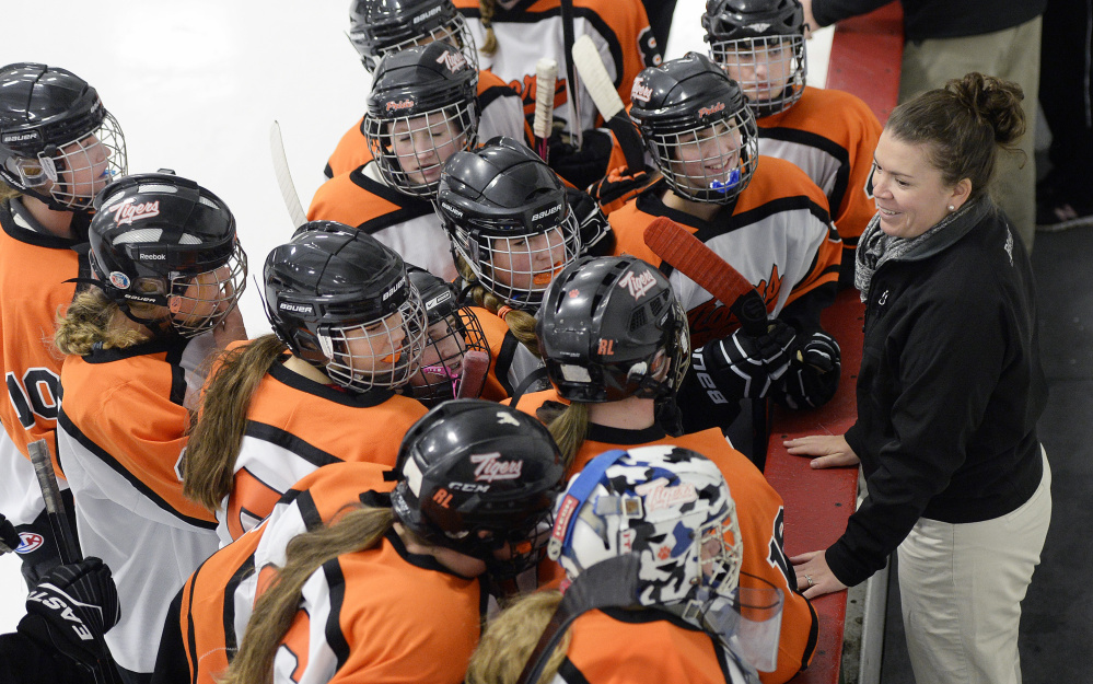 Biddeford Coach Ashley Potvin talks with her girls' hockey players, who are part of the team regardless of the rivalry in other sports. Of the 28 girls on the roster, 23 are from Biddeford and five from Thornton Academy in Saco.