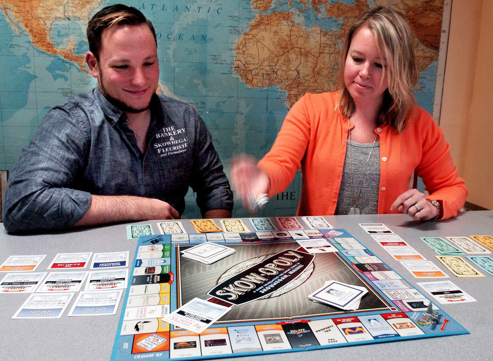Matt DuBois, co-owner of The Bankery and president of the Main Street Skowhegan board, and Executive Director Kristina Cannon begin a round of the Skowopoly board game at the Skowhegan office on Wednesday.  David Leaming/ Morning Sentinel