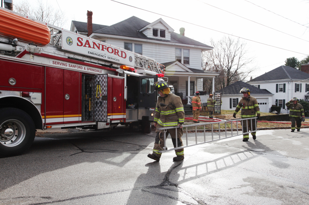 Sanford firefighters, helped by several surrounding departments, clean up after fighting a fire Saturday morning.