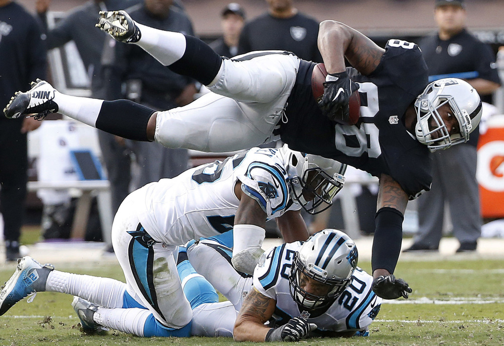 Raiders tight end Clive Walford is upended by Carolina's Kurt Coleman (20) during Oakland's 35-32 win Sunday.