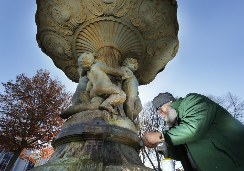 Jonathan Taggart, a sculpture restorer from Georgetown, works at loosening bolts on the fountain in Lincoln Park in Portland on Monday. The fountain sculpture, which was installed in 1871, will be removed Tuesday and Taggart will restore it over the winter.