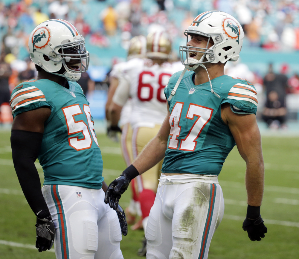 Miami's Kiko Alonso, right, celebrates an interception with teammate Donald Butler during a 31-24 win Sunday over the San Francisco 49ers at Miami Gardens, Fla.