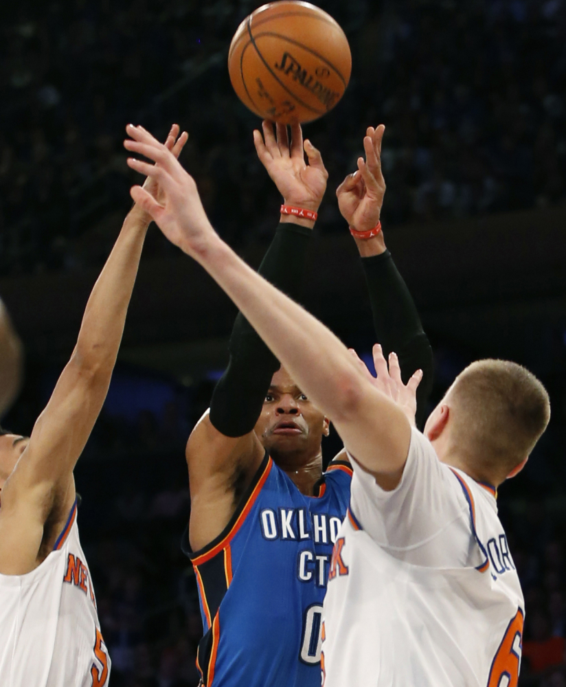 Oklahoma City guard Russell Westbrook shoots between Knicks defenders Courtney Lee, left, and Kristaps Porzingis during a 112-103 win by the Thunder at New York on Monday.