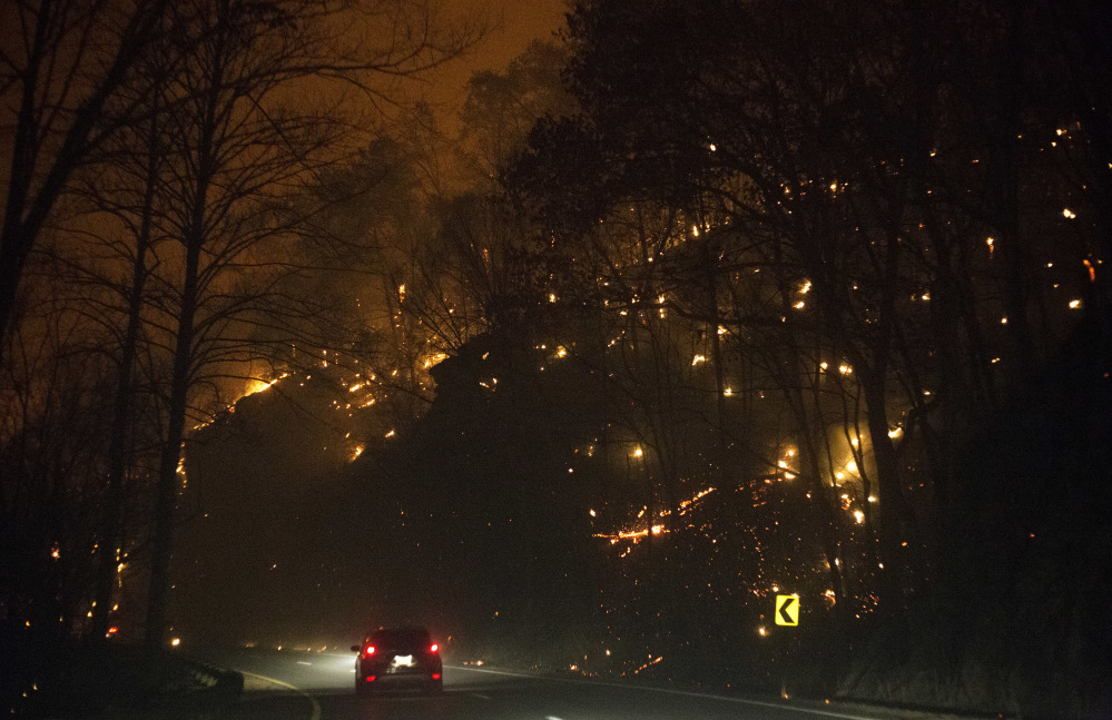 Fire erupts on both side of Highway 441 between Gatlinburg and Pigeon Forge, Tenn., Monday, Nov. 28, 2016. In Gatlinburg, smoke and fire caused the mandatory evacuation of downtown and surrounding areas, according to the Tennessee Emergency Management Agency.