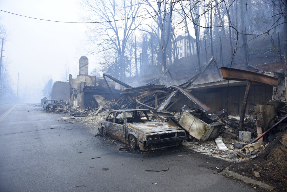 A structure and vehicle are damaged from the wildfires around Gatlinburg, Tenn., on  Tuesday, Nov. 29, 2016.  Rain had begun to fall in some areas, but experts predicted it would not be enough to end the relentless drought that has spread across several Southern states and provided fuel for fires now burning for weeks in states including Tennessee, Georgia and North Carolina.