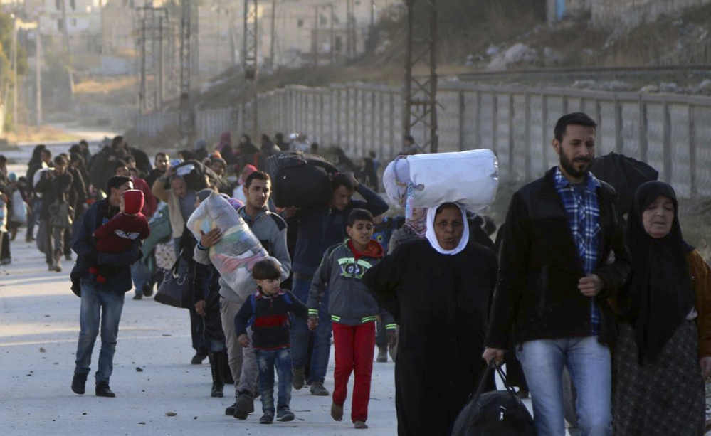 People flee rebel-held neighborhoods in eastern Aleppo on Sunday. A military official estimates that 20,000 people fled the area on Tuesday alone.