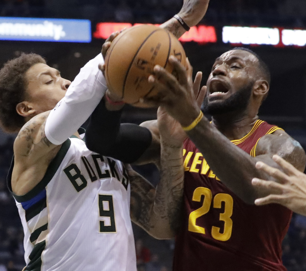Cleveland's LeBron James is fouled by Milwaukee's Michael Beasley in the first half Tuesday night in Milwaukee. The Bucks won by 17.