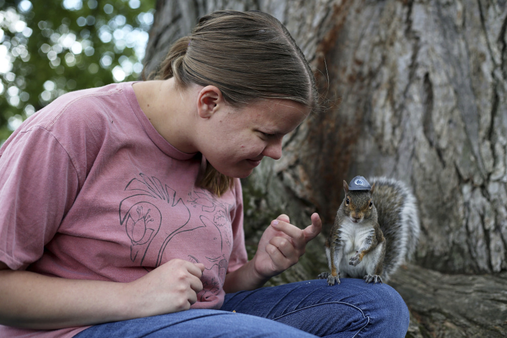 Penn State senior Mary Krupa plays with Sneezy the squirrel on Old Main Lawn in State College, Pa., in September.