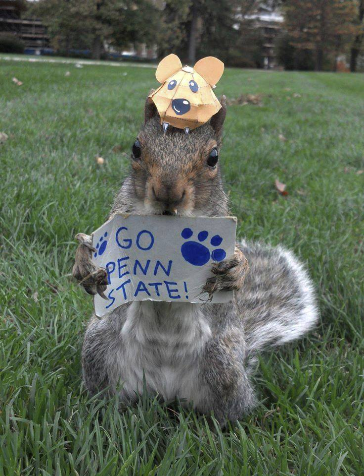 The current Sneezy, a squirrel that lives on the Penn State campus, wears a hat and holds a Go Penn State sign.