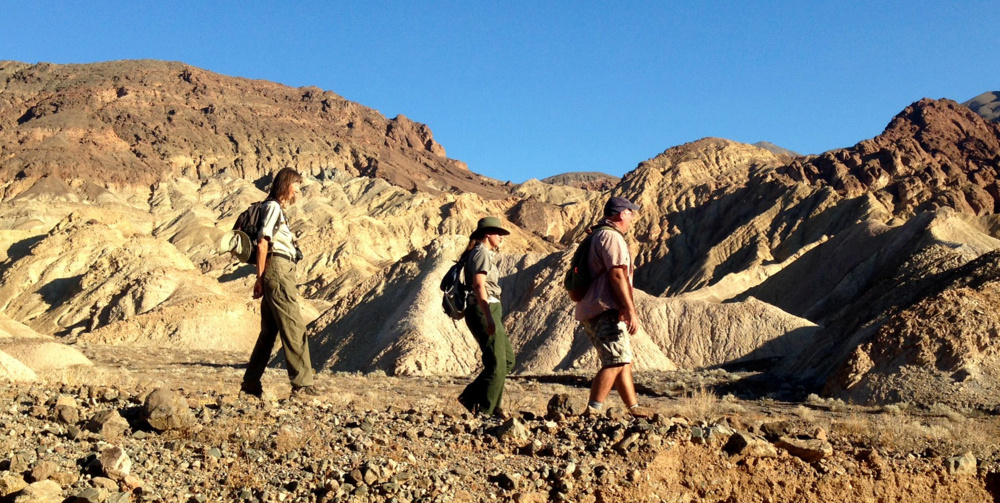 Naturalist Birgitta Jansen, from left, National Park Ranger Abby Wines and Loma Linda University paleontologist Torrey Nyborg following a trail that contains one of the largest concentrations of fossil tracks in the world.
