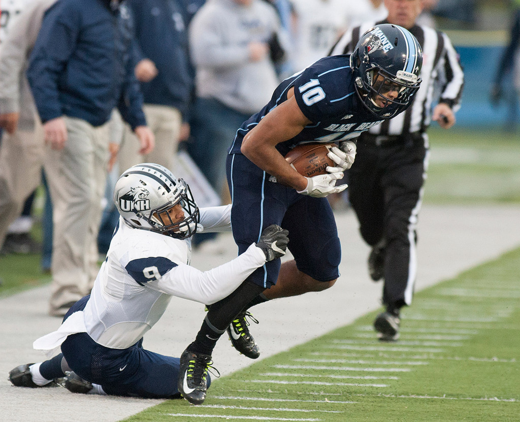 UMaine's Micah Wright is pulled out of bounds by  UNH's Isiah Perkinsduring the second half of Saturday's game in Orono.