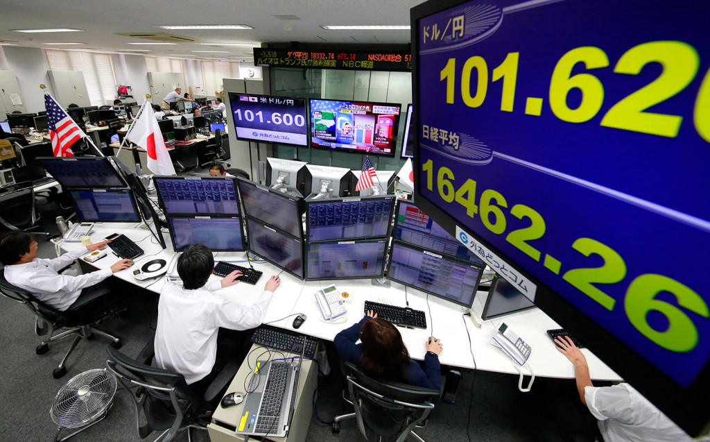 Money traders watch computer screens with the day's exchange rate between yen and the U.S. dollar at a foreign exchange brokerage in Tokyo on Wednesday. Asian markets tumbled as Donald Trump gained the lead in the electoral vote count in the presidential election.