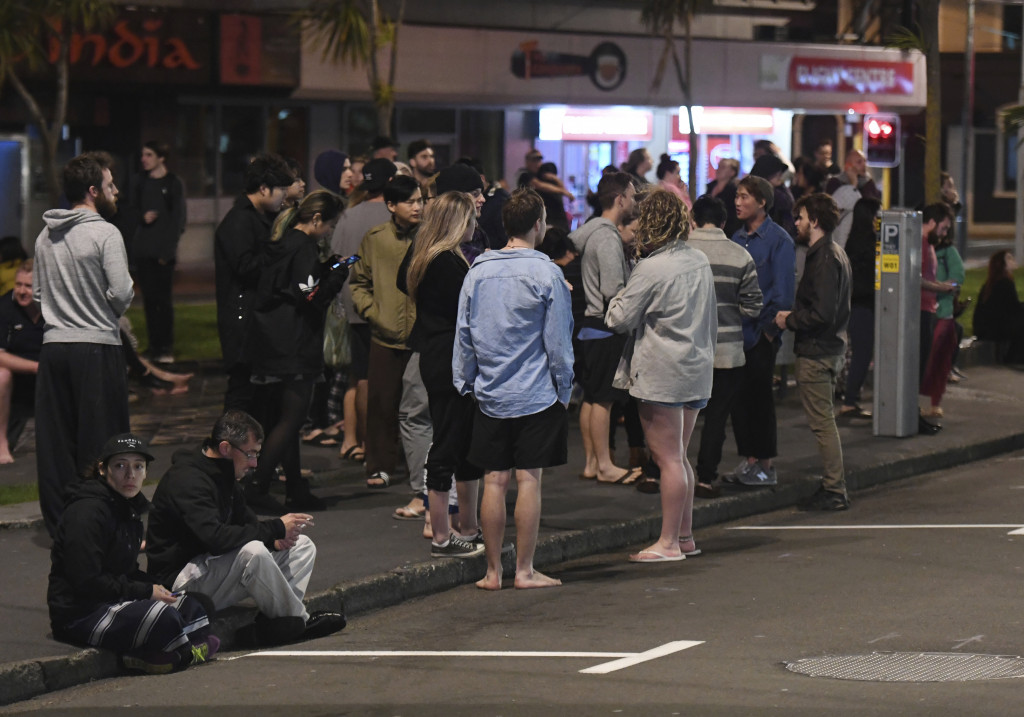 People evacuate from buildings in Wellington, New Zealand, after an earthquake on Monday.