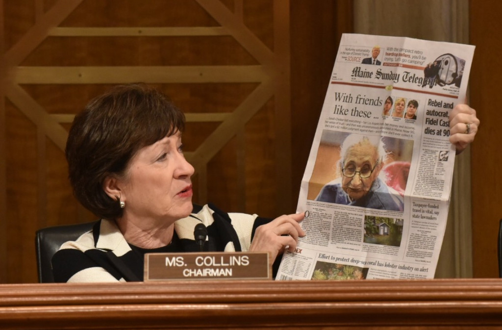 Sen. Susan Collins holds up the Nov. 27 edition of the Maine Sunday Telegram, which featured a story about a woman who lost her home and savings to a group of people who befriended her in California and drove her across the country, abandoning her in Maine.