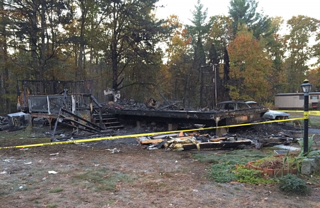 The charred frames of two walls and the porch stairs were the only identifiable pieces of the house remaining Tuesday morning. <em>Photo by Gillian Graham/Staff Writer</em>