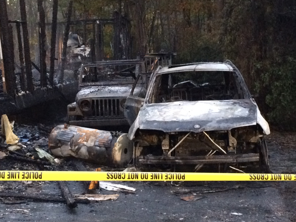 Two badly burned cars sit in the driveway next to the trailer that was destroyed in the explosion and fire.
