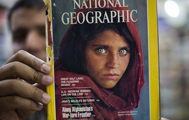 A copy of the 1984 National Geographic magazine with the photograph of Afghan refugee woman Sharbat Gulla.