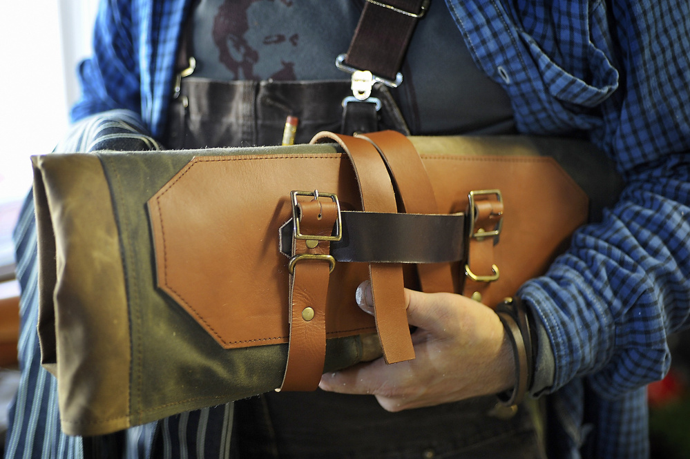 Erik Desjarlais holds one of his handmade knife rolls at Weft & Warp in this photo from 2015. Desjarlais is offering leatherworking classes this winter.