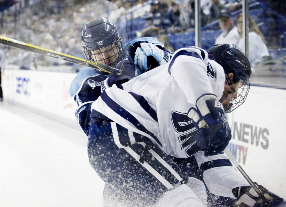 Dylan Maller of New Hampshire, foreground, competes for the puck along the boards with Mitchell Fossier of Maine during their Hockey East game. The teams will meet again Saturday night at Orono.