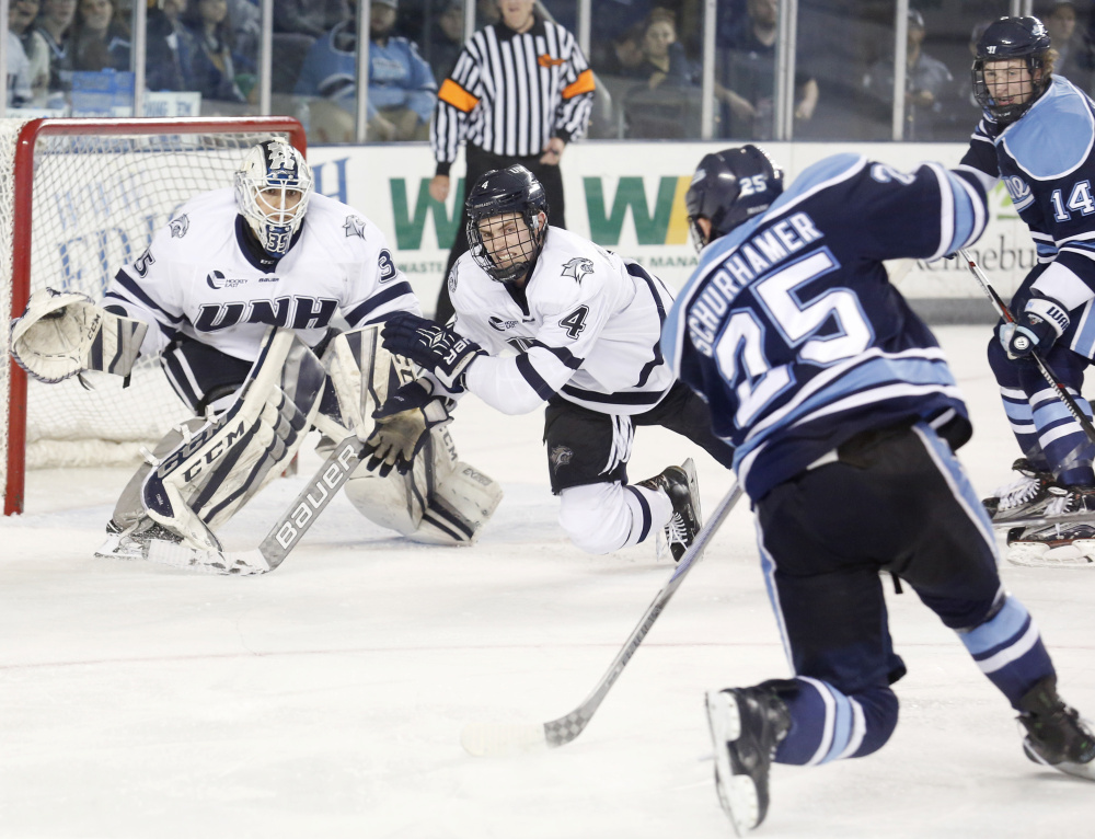 Eric Schurhamer of Maine unleashes a shot in the third period Friday night as Dylan Maller of New Hampshire looks to block it in front of goalie Danny Tirone. New Hampshire scored two goals in the second period and three in the third for a 5-1 victory at home.