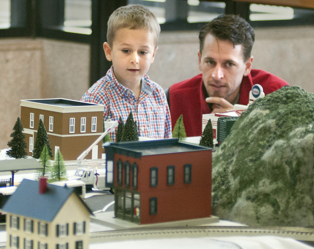 Lincoln Haiss, 5, and his father, Josh Haiss, check out a layout Friday in the atrium of the Cultural Building. The show is one of the museum's most popular events.