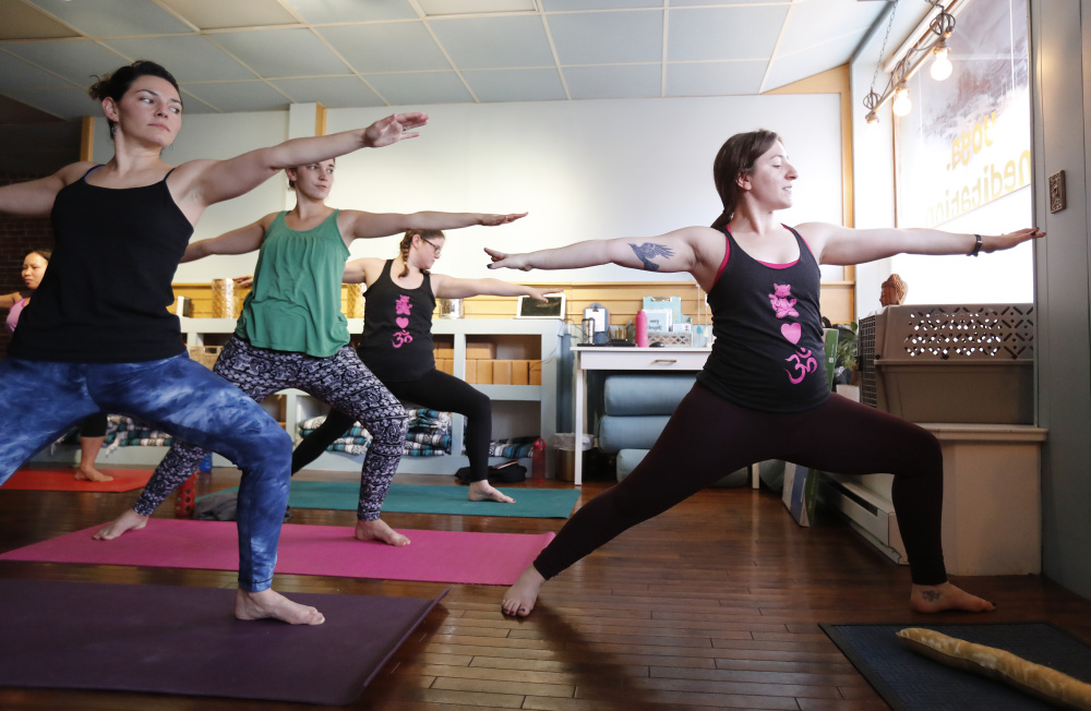 Sarah Spiegel, right, leads a yoga class Saturday in Saco. Joel Page/Staff Photographer