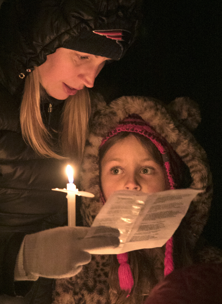 Rebecca Plamondon of Kennebunkport, left, and her daughter Ayla go caroling at the Franciscan monastery in Kennebunk during Christmas Prelude on Saturday. Gregory Rec/Staff Photographer