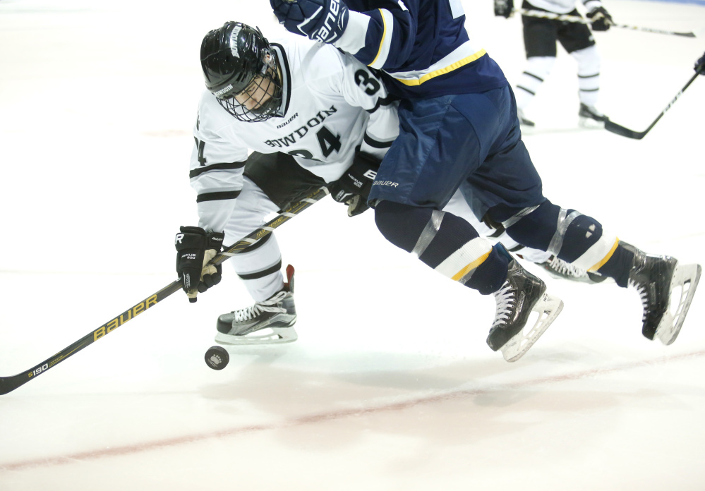 Bowdoin's Ronnie Lestan tries to handle the puck as he takes a check during the Polar Bears' 3-0 victory over the University of Southern Maine on Tuesday in Brunswick.