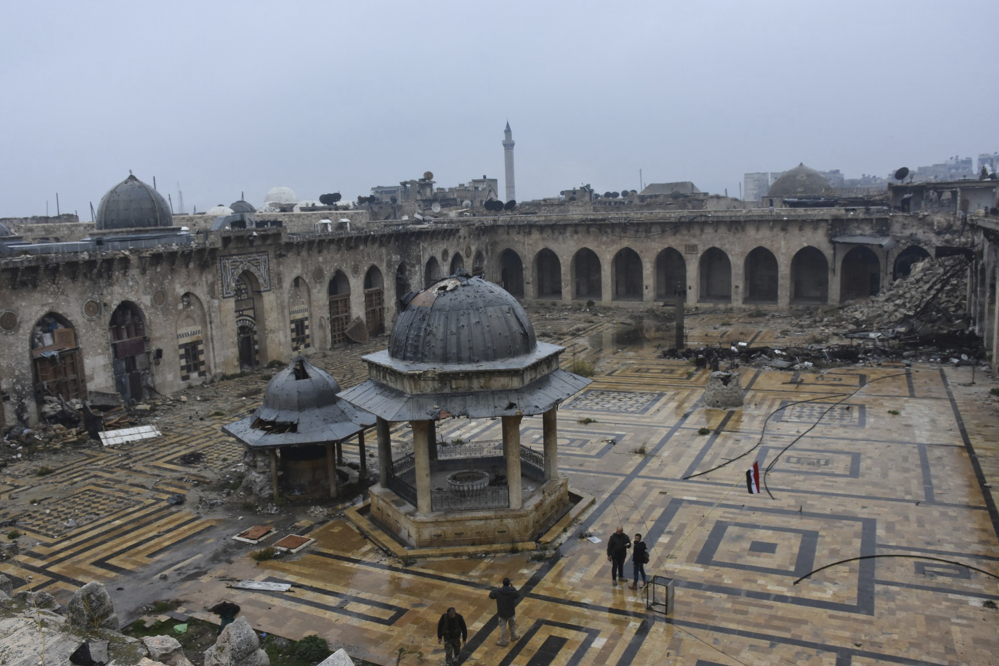 Syrian troops and pro-government gunmen walk inside the destroyed Grand Umayyad mosque in the old city of Aleppo, Syria, on Tuesday. Government forces and rebel fighters have fought to control the 12th-century mosque for the last four years, until Syrian troops seized control of it this week.