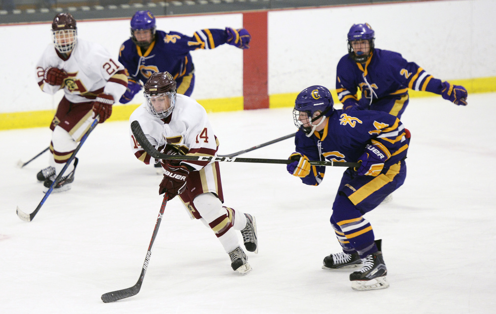 Thornton Academy's Noah Logan skates with the puck as Justin Ray of Cheverus moves in during Wednesday's game at the Biddeford Ice Arena. Cheverus earned a 4-2 win. (Shawn Patrick Ouellette/Staff Photographer)