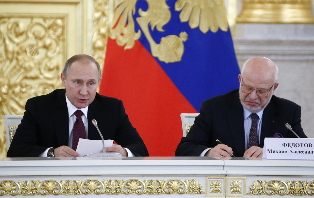Russia's President Vladimir Putin, left, delivers a speech during a session of the Council for Civil Society and Human Rights, as its chairman Mikhail Fedotov sits at right at the Kremlin in Moscow, Russia, on Thursday.