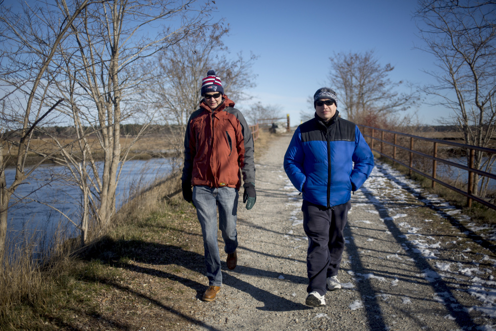 Ron Currier, left, and Jack Currier, of Scarborough, walk along the section of the Eastern Trail that goes through the Scarborough Marsh. The $100,000 gift will be earmarked to build a bridge over the Nonesuch River, filling a gap in the trail between Scarborough to South Portland. <em>Brianna Soukup/Staff Photographer</em>