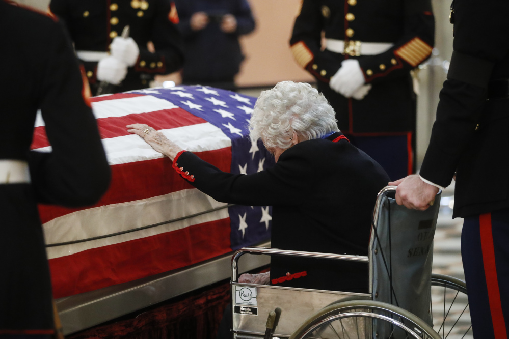 Annie Glenn touches the casket of her husband John Glenn as he lies in honor, Friday, Dec. 16, 2016, in Columbus, Ohio. Glenn's home state and the nation began saying goodbye to the famed astronaut who died last week at the age of 95. (AP Photo/John Minchillo)