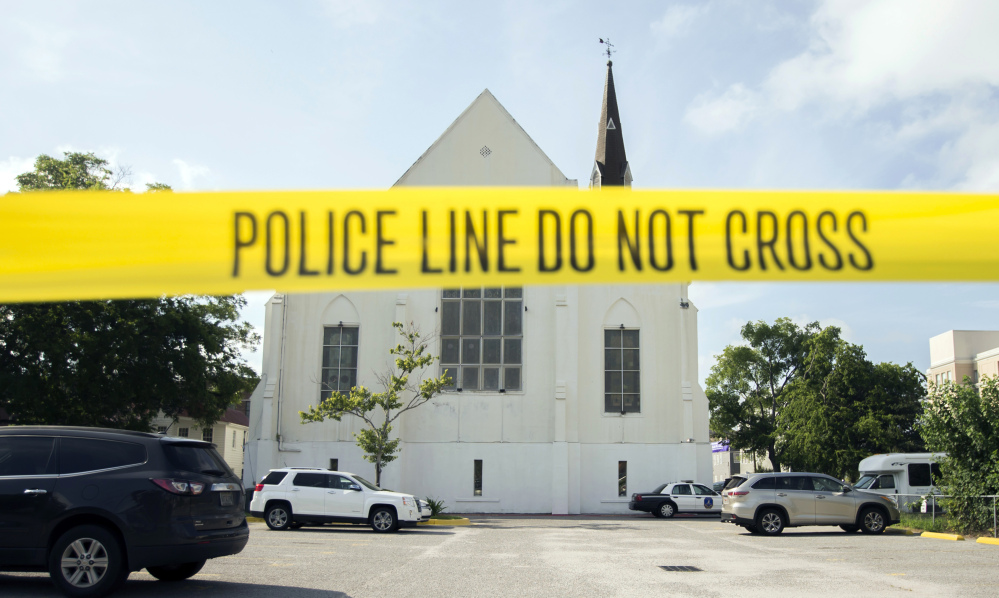 Police tape surrounds the parking lot behind the AME Emanuel Church where Dylann Roof shot and killed nine members of the church Bible study. Some in Charleston are struggling with the concept of forgiving Roof.