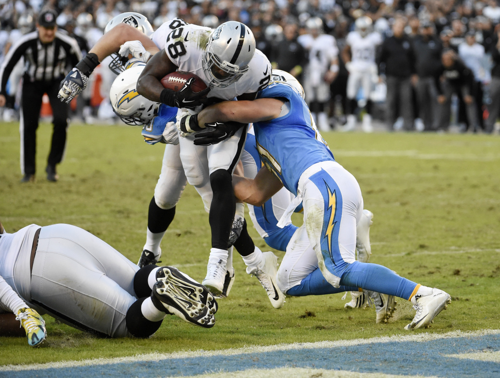 Oakland Raiders running back Latavius Murray (28) is held out of the end zone by San Diego Chargers outside linebacker Kyle Emanuel, right, and defensive end Joey Bosa, behind, during the second half of an NFL football game Sunday, Dec. 18, 2016, in San Diego. (AP Photo/Denis Poroy)