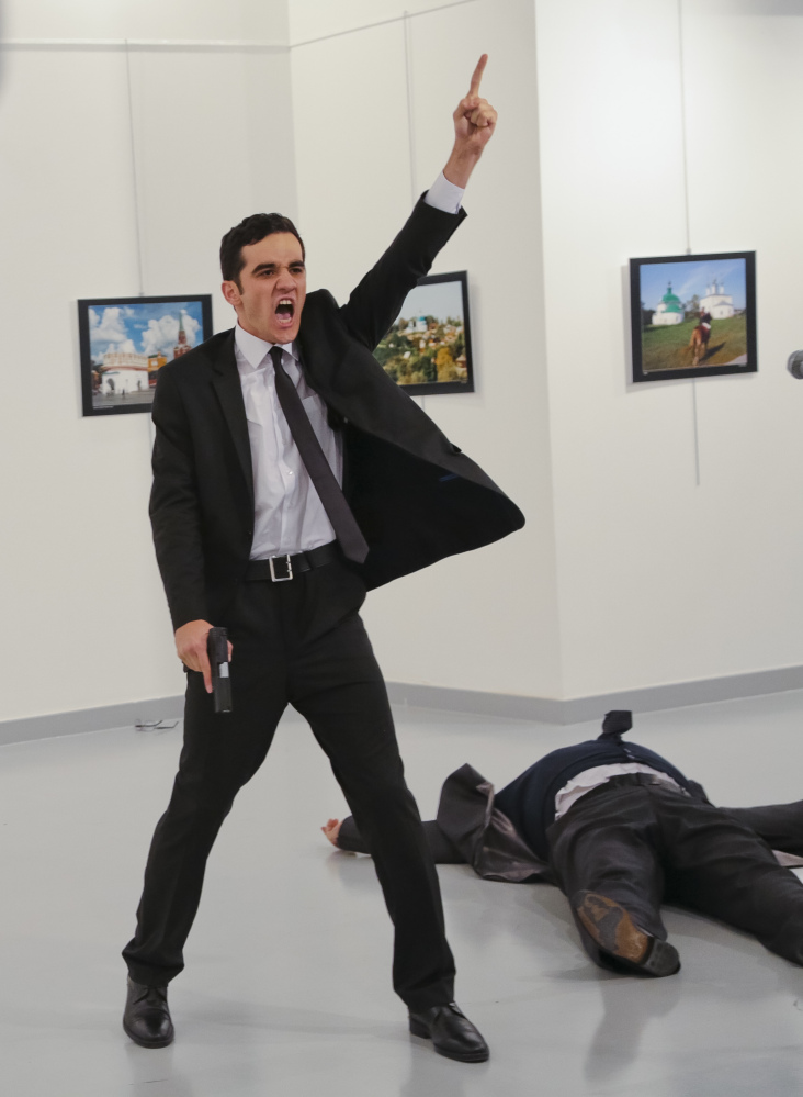 A gunman identified as Mevlut Mert Altintas, who had been an officer with Ankara's riot police squad for more than two years, gestures after shooting the Russian ambassador to Turkey, Andrei Karlov, at a photo gallery in Ankara, Turkey, on Monday.
