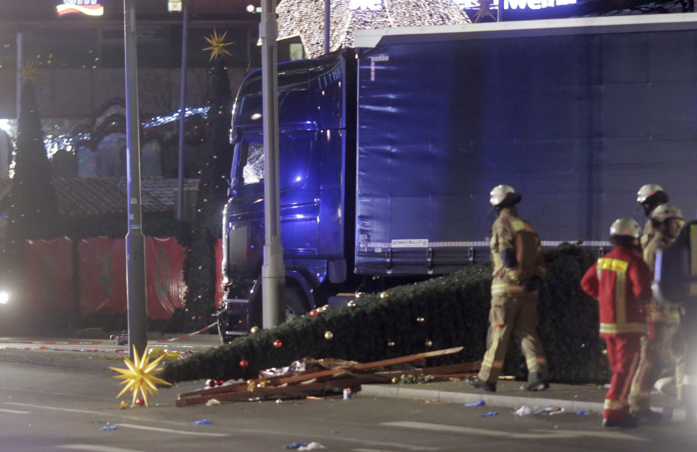 Firefighters stand beside the truck that ran into a crowd in Berlin.