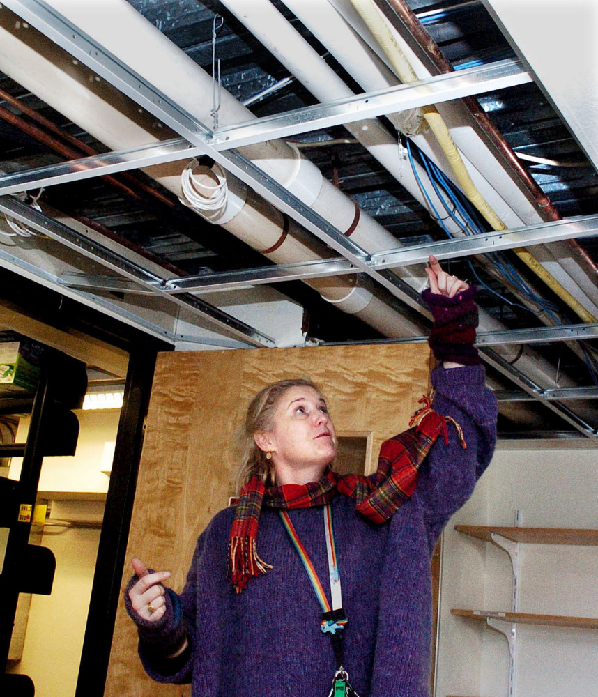 At left, Waterville Public Library Director Sarah Sugden identifies the pipe that burst, drenching about 50 nonfiction children's books. Above, CDs, audiobooks and cases are spread out to dry Monday at the library. Carpeting in two rooms, ceiling tiles, walls and the lobby floor were also damaged.