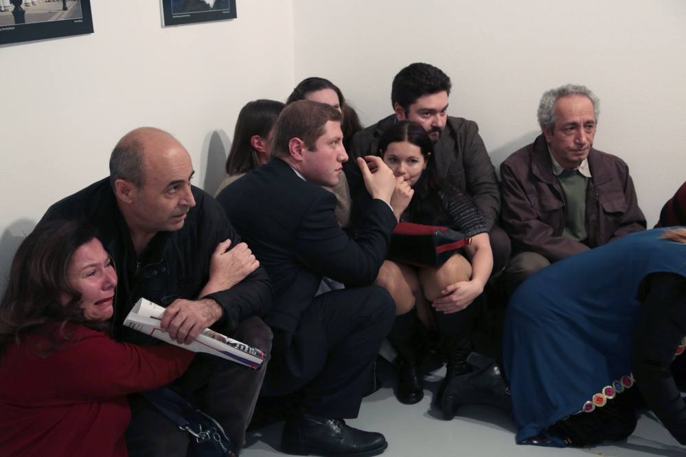 People crouch in a corner after Andrei Karlov, the Russian ambassador to Turkey, was shot at a photo gallery in Ankara, Turkey, on Monday. Turkey and Russia plan to work together to investigate the assassination.