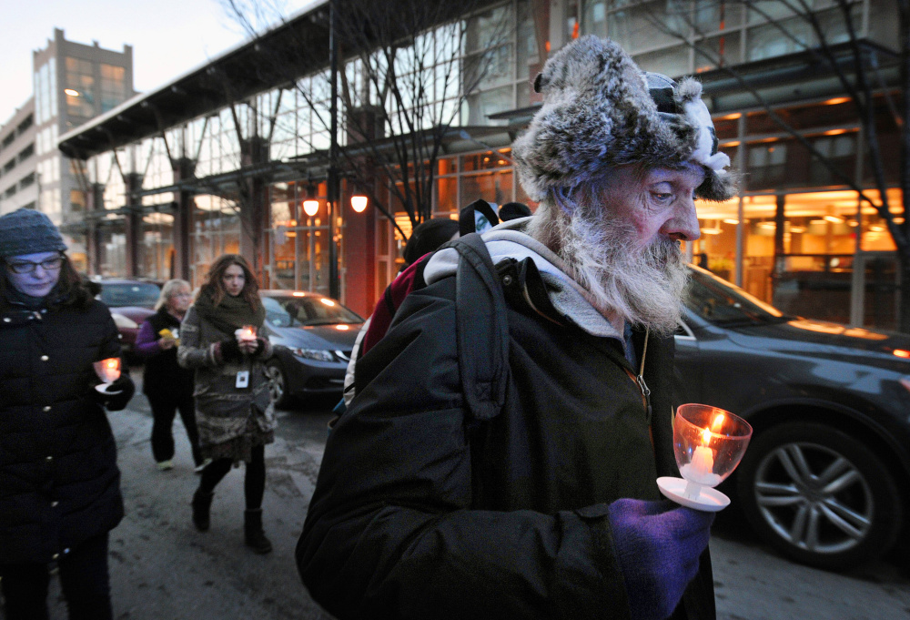 Alan Libby, who is homeless, marches up Preble Street during Wednesday's vigil in Portland. Libby, who will move to a home in Rumford in January, said he was participating in the event to remember his friend Randy, who died a week ago. During the annual vigil, held on the evening of the winter solstice, Portland mourns the loss of its most vulnerable; this year, 32 homeless people died in the city.