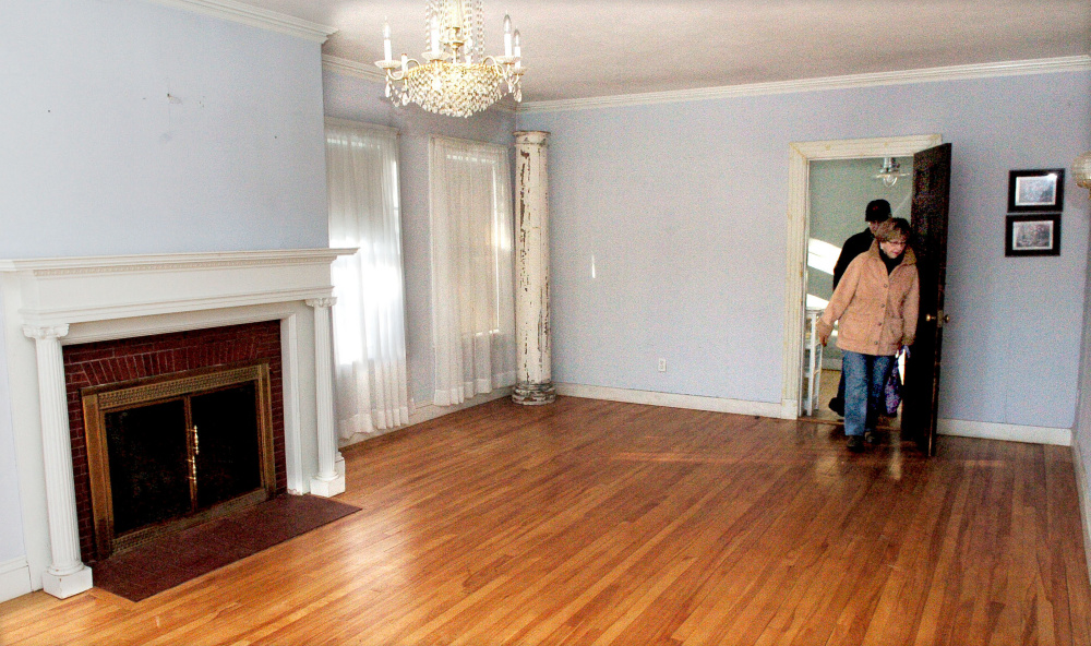 Potential bidders tour the Skowhegan home formerly owned by Dale Thistle that was sold at an auction for $130,000 on Wednesday. A local building contractor and his wife submitted the higher of two bids for the property.