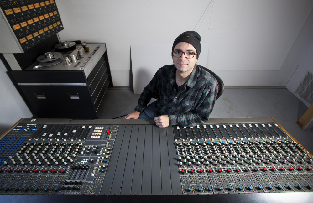 Nick Johnson, who plans to operate an old fashioned tape recording studio in Portland, sits behind a recording console that he picked up in New Jersey.