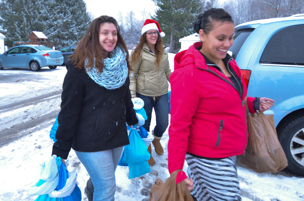 From left, Kaplan University students Liz Ponds, Miranda Costigan and Leleshia O'Neil carry bags of food and personal items for veterans living at the Bread of Life shelter in Augusta.