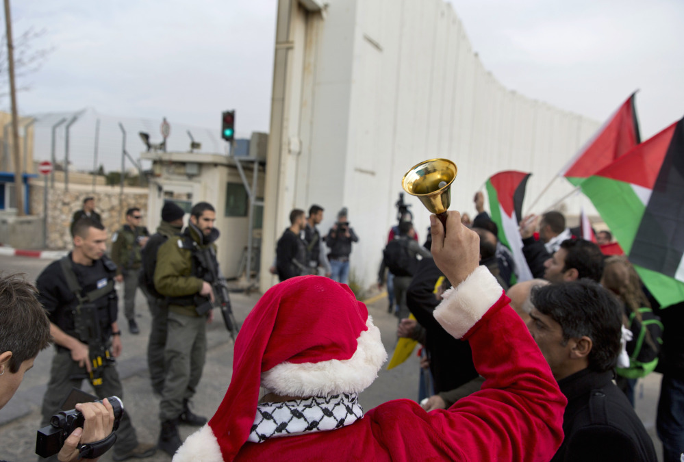 """Palestinian protesters, some dressed as Santa Claus, carry Palestinian flags and chant anti Israel slogans during a protest in front of an Israeli checkpoint, in the West Bank city of Bethlehem, Friday. In a Christmas greeting on Friday, Palestinian President Mahmoud Abbas said: """"Despite the Israeli occupation, our presence in our homeland and the preservation of our cultural and national heritage are the most important form of resistance in the face of the darkness of a foreign colonialist occupying power."""""""