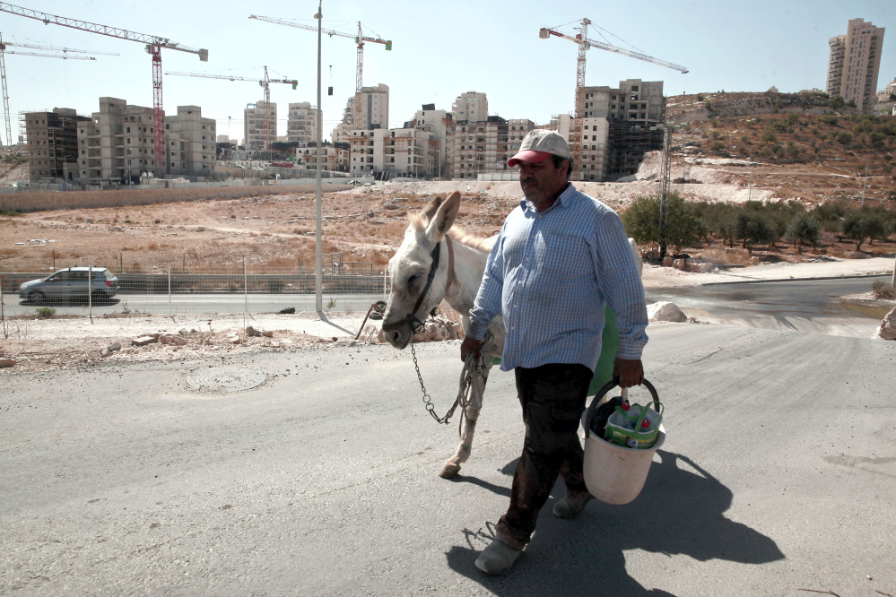 A Palestinian man walks near a construction site of a new housing unit in the east Jerusalem neighborhood of Har Homa. The U.N. Security Council on Friday condemned Israel's settlements and continuing construction in Palestinian territory as a 'flagrant violation' of international law.