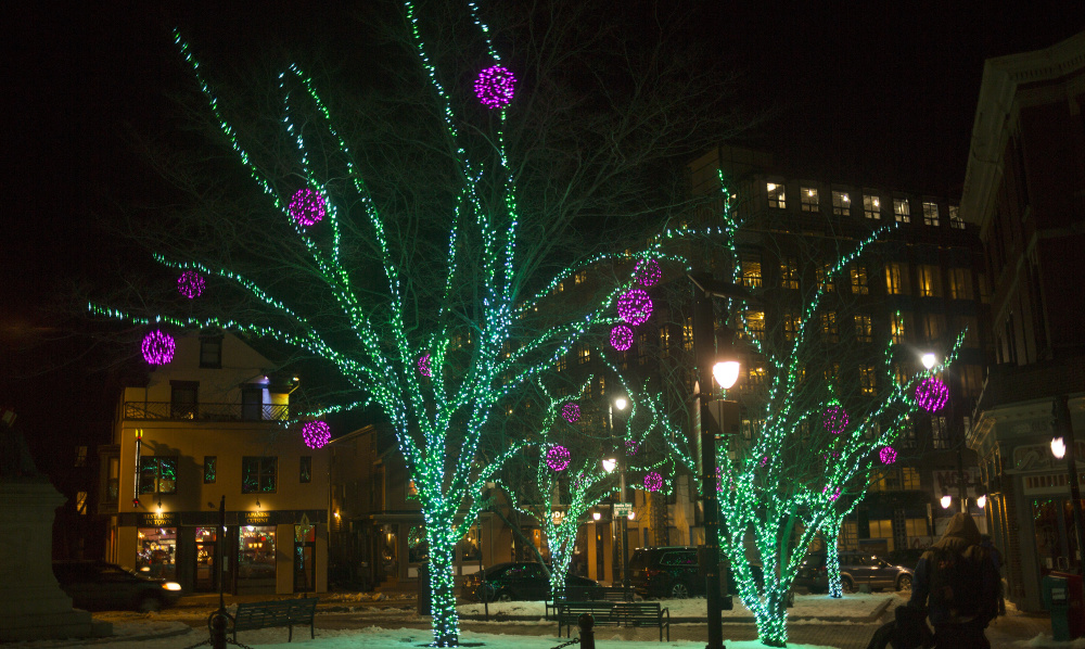 Trees covered in holiday lights brighten up Longfellow Square in Portland. The traditions observed in America's Christmas come from all corners of the Earth and from observances both religious and secular.