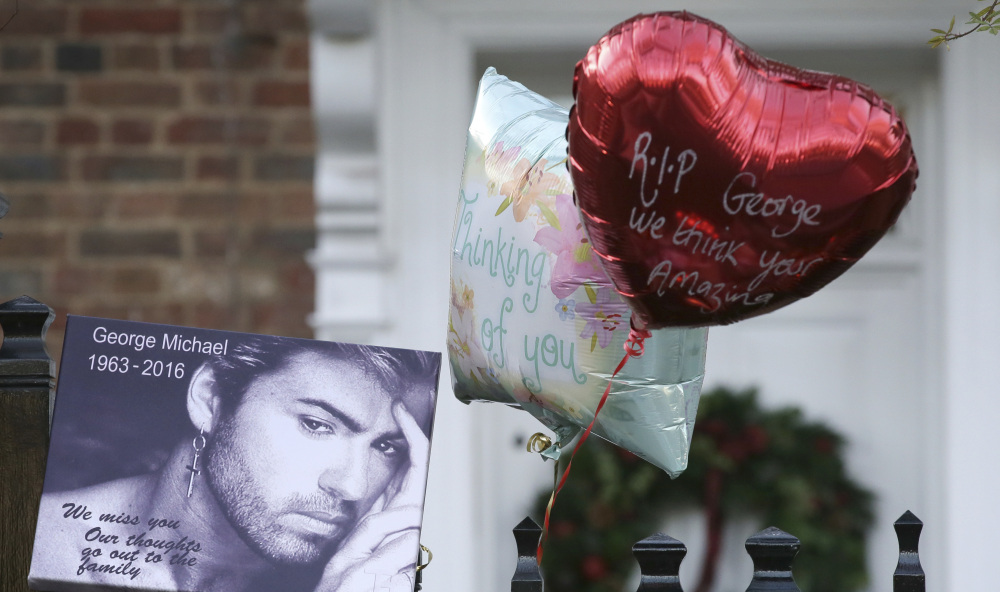 Tributes are left on the gate outside the home of British musician George Michael in London on Monday. Michael died of apparent heart failure at age 53.