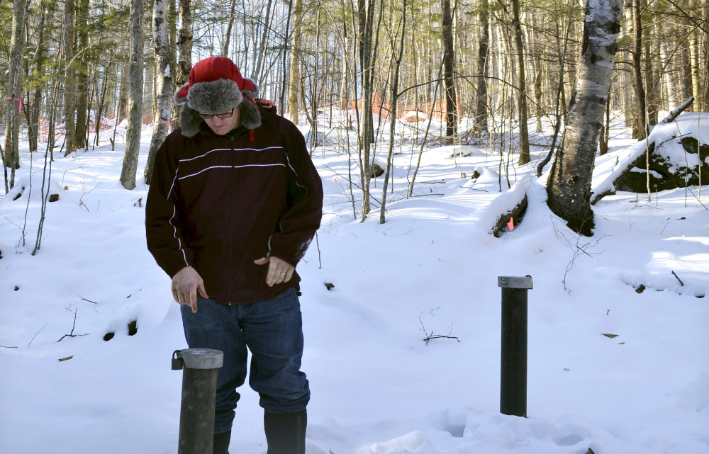 Richard Higgins, whose family's well water has been contaminated by a suspected carcinogen from a Dartmouth College dump site, looks down at one of many test wells installed to monitor the groundwater in Hanover, N.H.