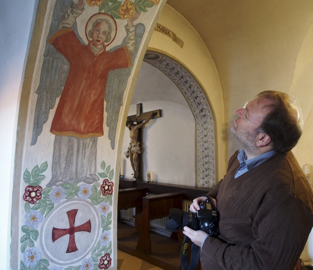 Historian Volker Schier views a mural in the abbey in Altomuenster, Germany. He estimates that the abbey's library holds around 80 percent of the order's books.